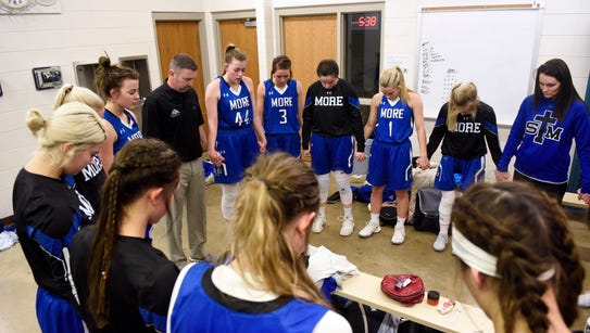 The St. Thomas More team prays before their high school