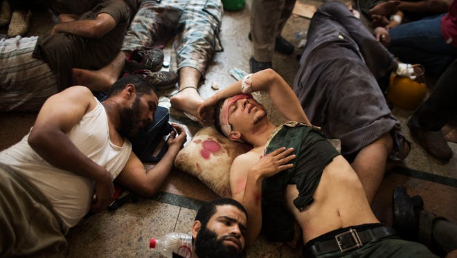 Wounded supporters of ousted Islamist president Mohammed Morsi lie on the floor of a makeshift hospital at a sit-in camp in Cairo.