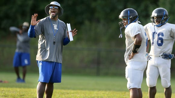 La Vergne Head Coach Stanton Stevens works with players during the school's first day of pracitce with full pads on Monday, July 27, 2015.
