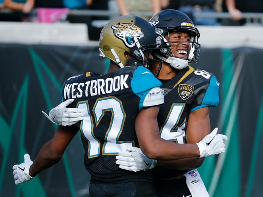 Jacksonville Jaguars wide receiver Keelan Cole, right, celebrates a 73-yard pass play to set up a touchdown against the Houston Texans with teammate wide receiver Dede Westbrook (12) during the second half of an NFL football game, Sunday, Dec. 17, 2017, in Jacksonville, Fla. (AP Photo/Stephen B. Morton)