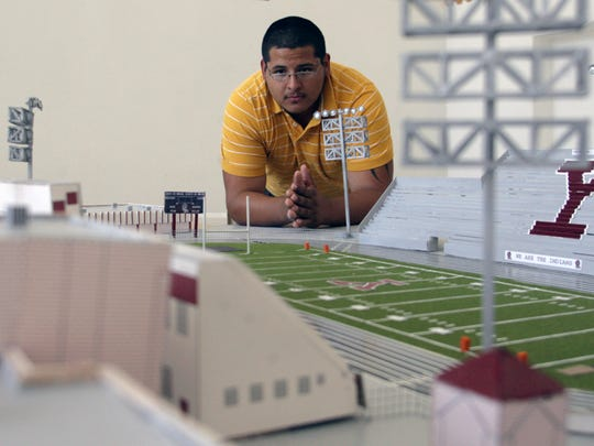 In this June 12, 2010 file photo Ysleta High School graduate Jesse Hinojos looks at his 1/8-inch scale model of Ysleta High School's Hutchins Stadium.