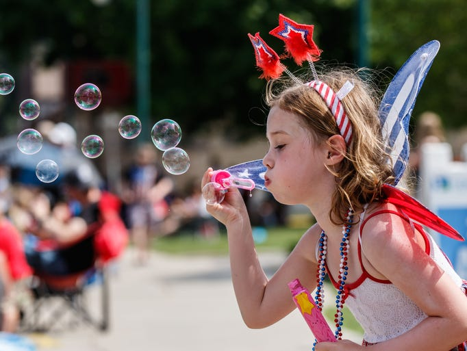 Five-year-old Ellie Lach of Pewaukee blows bubbles