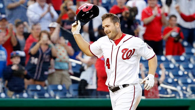 Nationals center fielder Chris Heisey tosses his batting helmet after hitting the game-winning home run in the 16th inning at Nationals Park.