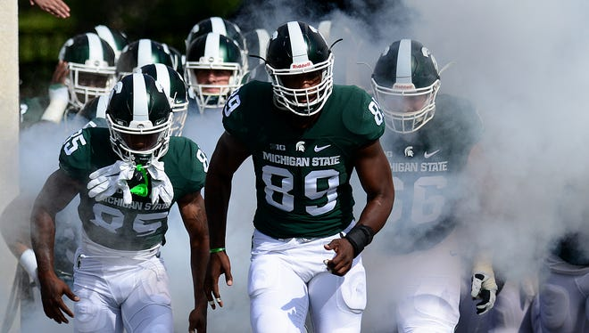 Michigan State defensive end Shilique Calhoun (89) leads the team onto the field before the start of the Spartans' game with Central Michigan Saturday at Spartan Stadium.