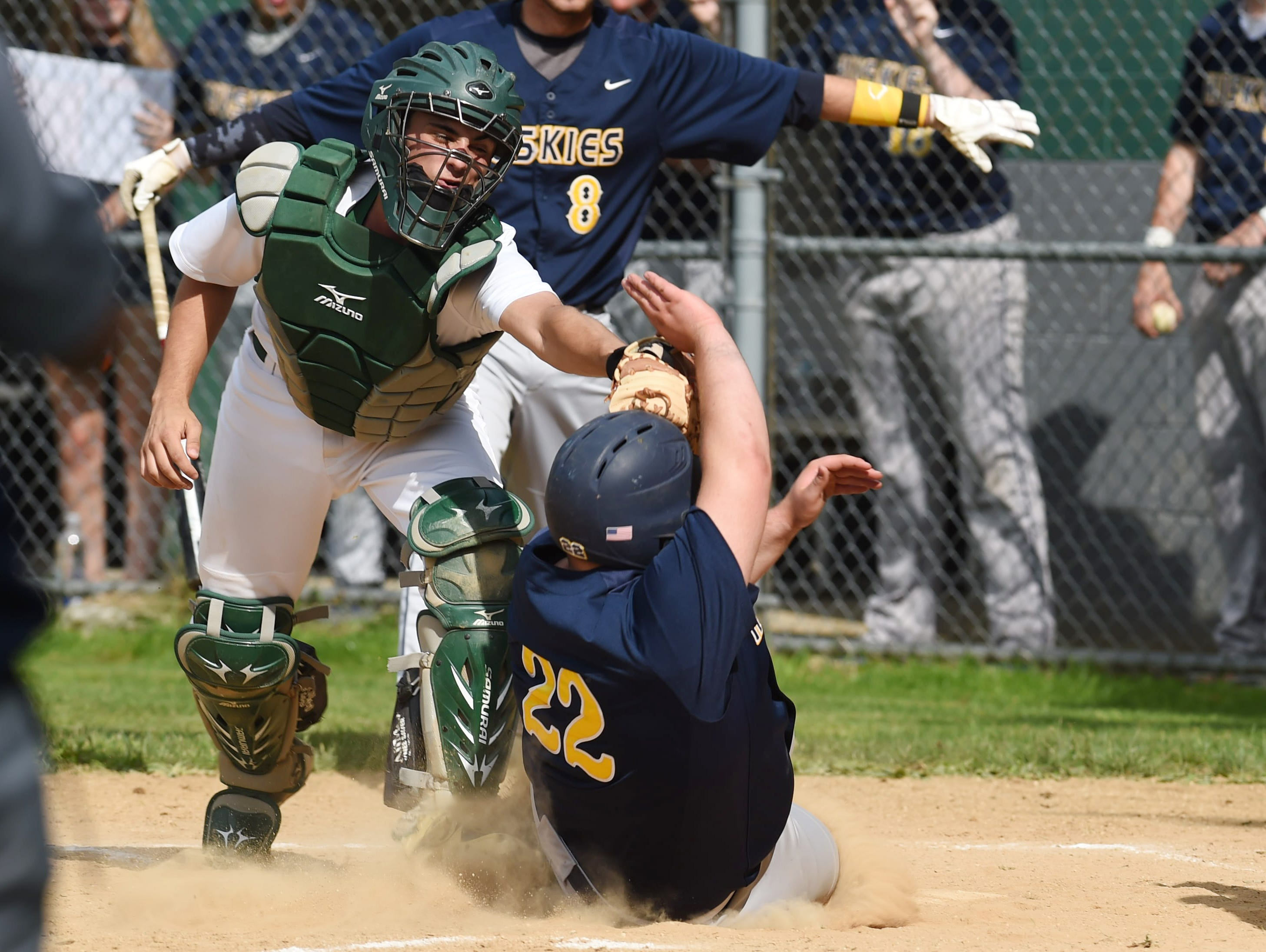 Spackenkill's Joe Arcuri, left, tags out Highland's Frank Alfonso, right, at home plate during Monday's game.