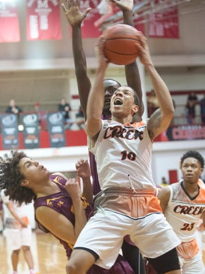 Fern Creek guard Ahmad Price puts up a shot colliding with Doss guard Taye Calloway, left. Behind him is Doss forward ShawnKel Knight-Goff and at right is Fern Creek guard-forward Tony Rogers. Jan. 20, 2018
