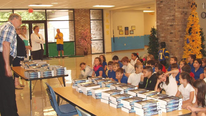 Ray Schrock with the Pineville Rotary Club talks to kids before handing out dictionaries, one of the club's annual projects.