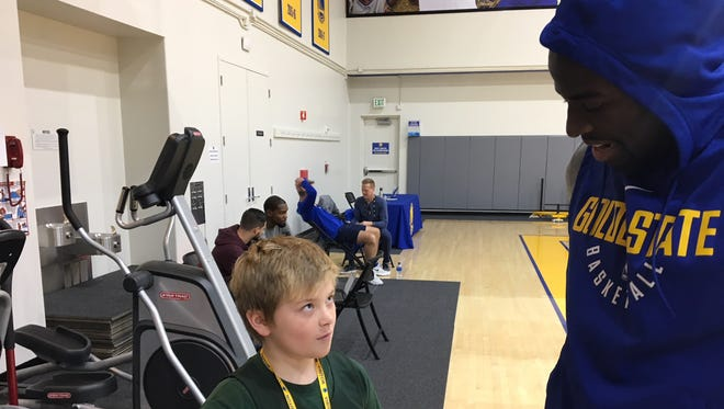 Golden State Warriors forward Draymond Green talks with Brennan Rexrode on Wednesday at practice in Oakland, Calif.