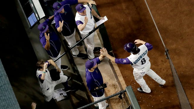 Arizona Diamondbacks' Tuffy Gosewisch (8) is greeted at the dugout after scoring during the third inning of a baseball game against the Los Angeles Dodgers on Thursday, Sept. 15, 2016, in Phoenix.