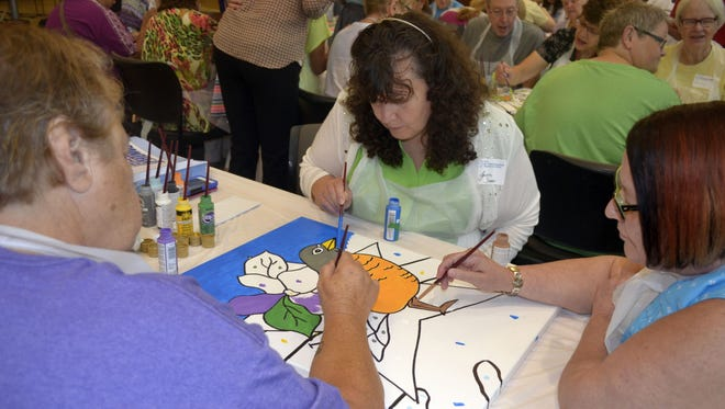 From left, cancer survivors Kay Virt of Green Bay, Jean Fameree of Kenosha and Joanne Fameree of Casco paint a special canvas for Wisconsin that features the state bird (American robin) and state flower (wood violet) for the PaintFest America project at HSHS St. Mary's Hospital Medical Center in Green Bay on Thursday, Aug. 11, 2016. The Famerees are sisters. The Wisconsin panel will be added to a 50-state mural that will be displayed Aug. 23 in New York City for the culminating event of this summer's PaintFest America sponsored by the Foundation for Hospital Art in Marietta, Ga.