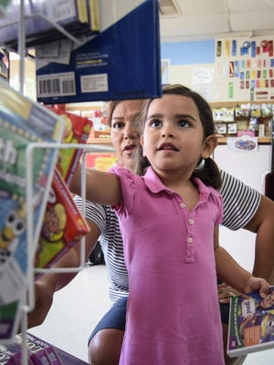 """Naitea Sanchez Wooley, 3, of Tamuning, picks out an educational DVD with help from her mother, Amanda G.S. Wooley, at School Essentials in Tamuning on July 28. Wooley opted for a purple-colored DVD, stating  """"I like purple."""""""