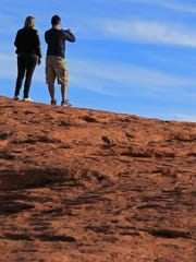 Hikers take pictures of St. George from on top of the Sugarloaf.