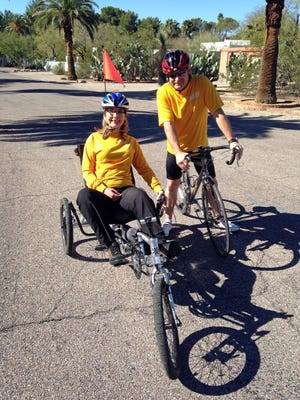 In this February 2015 photo provided by Mark Prentice, former Congresswoman Gabrielle Giffords and husband Mark Kelly, founders of the advocacy group Americans for Responsible Solutions,  pose for a photo in Tucson as they train for a 40-mile charity ride called El Tour de Tucson.