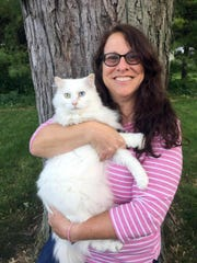 Veterinarian Dr. Janet Cohn holds Teddy, a patient's cat, during a house call in Arlington, Ohio. Veterinarians are making house calls and teaching tricks to pets of aging baby boomers.