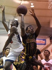 Columbus Falcon Javonte McDavid (2) gets by Forest Hill's Thomas Grayson for a layup on Friday at Forest Hill High School.