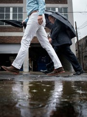 Pedestrians walk on 2nd Ave South during rainfall on Thursday in Nashville.