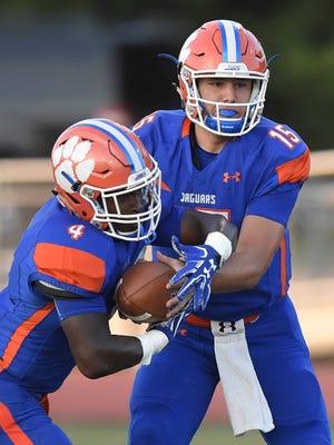 Madison Central quarterback Jack Walker (15) hands off to Gabe Short (4) on Friday, September 2, 2016, at Madison Central High School in Madison, Miss.