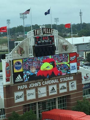 ESPN 'College GameDay' co-host and former U of L coach Lee Corso sports a Cardinal head as he makes his pick Saturday at Papa John's Cardinal Stadium.