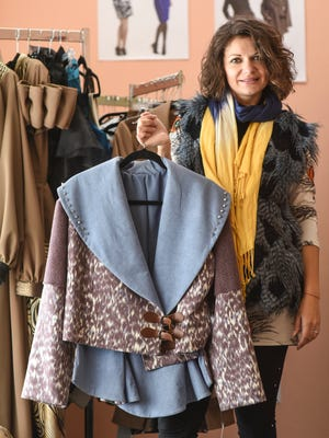 Mila Pershyna shows a jacket she designed while studying for her master's degree at Wayne State University. It's part of a sample sale at her Sylvan Lake studio.