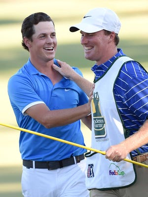 Tournament champion Cody Gribble (left) and his caddy Bobby Hudson celebrate on the 18th green on Sunday, October 30, 2016, the final day of the Sanderson Farms Championship at the Country Club of Jackson in Jackson, Miss.