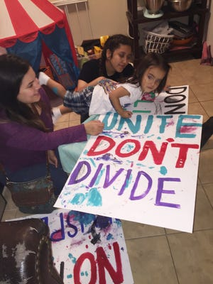 Melanie Villela, 30, of Houston paints posters she will use in protests with her children Destiny, 13, and Joseph, 2.