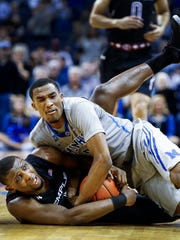 University of Memphis guard Jeremiah Martin (top) battles Temple University guard Daniel Dingle (bottom) for a loose ball during second half action of a 74-62 Tigers loss at the FedExForum. Memphis staged a vigorous second-half comeback, but could not a overcome a nearly 11-minute scoring drought that lead to 37.9 percent shooting on the game.