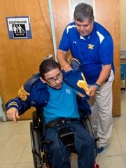 Teacher Rudy Rodriguez helps John Andrew Mendoza put on his letter jacket at Moody High School.  Mendoza is among the students who are part of the Special Olympics or honor roll to graduate with letterman jackets and honor chords.