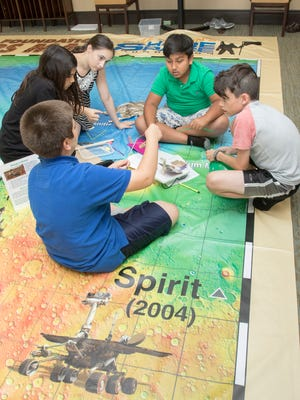 Montessori School of Pensacola students Omar Qader, 12, clockwise from left, Sophia Mehmood, 11, Brianna Jackson-Floyes, 11, Rakibe Islam, 9, and Nathan Carroll, 11, work on designing a model of rover to explore Mars during the school's weekly visit to Summer Vista Assisted Living in Pensacola on Tuesday, March 28, 2017.