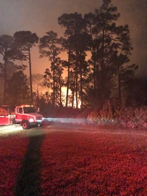 St. Lucie County Fire District crews respond to a wildfire Friday, April 7, 2017, off Northwest Peacock Boulevard near First Data Field in Port St. Lucie.