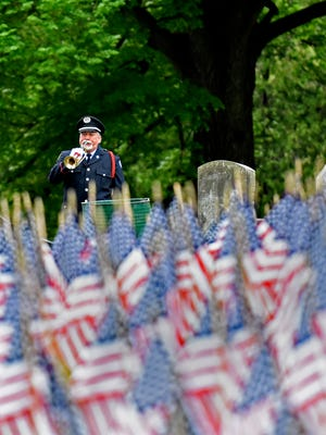 Bugler Kevin Baum plays taps during a short ceremony following the placement of 2,393 American flags as the Afghanistan War Flag Memorial is reinstalled at Prospect Hill Cemetery in York City, Saturday, April 22, 2017. An additional 303 state flags were also placed commemorating fallen Pennsylvanians who lost their lives in  Afghanistan and Iraq. Dawn J. Sagert photo