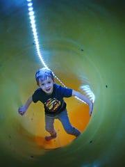 Leo Kuhl climbs up the tube slide in his bare feet. (Richard Tsong-Taatarii/Minneapolis Star Tribune/TNS)