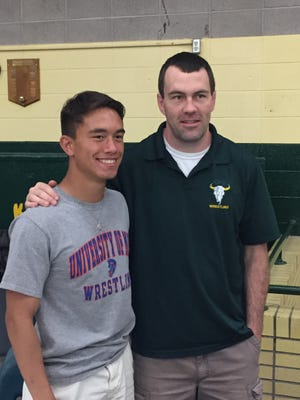 C.M. Russell High's Deven Altenburg-Lasher, left, standing with head coach Aaron Jensen. Altenberg signed his letter of intent to the University of Mary Thursday for wrestling.