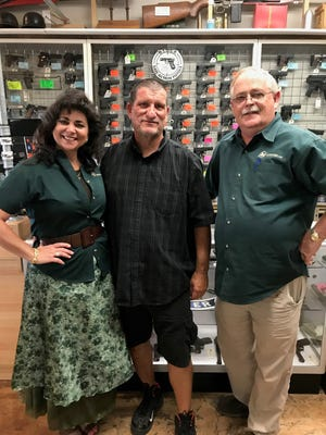 State Trooper Ed Andersson poses next to Cheryl and Dan Todd, owners of AZ Firearms, Gun Freedom Radio and Post of Gold Estate on May 24, 2017.