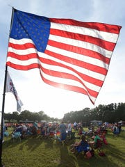 A large American flag flies over the gathered attendees