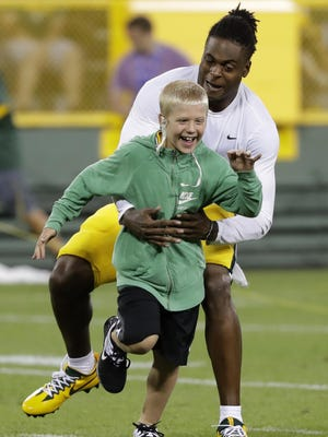 Packers wide receiver Davante Adams has some fun with Jordy Nelson's son, Royal, after the Family Night scrimmage in Green Bay on Saturday.