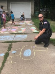 Wisconsin Rapids Police Lt. Brian Krzykowski creates some artwork with some newfound friends in the city Friday.