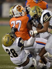 Madison Central's Cedric Beal (27) is gang tackled by the Pearl defense including Jarvis Townsend (28) and Trevontae Lewis (25) on Friday, September 15, 2017, at Madison Central High School in Madison, Miss.
