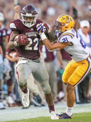 Mississippi State's Aeris Williams (22) tries to break free from LSU's Ed Paris (21) after a long gain.