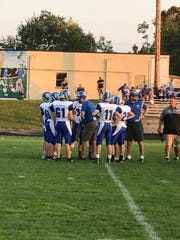 Amherst football coach Mark Lusic huddles with the