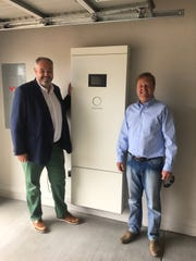 Christoph Ostermann (left), CEO of Sonnen and Dave Everson, CEO of Mandalay Homes, stand near the battery in the Prescott test home.