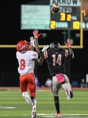 Warren Central's Demond Patton hauls in a long pass over Clinton's Chase Moore during Friday night's game in Clinton.