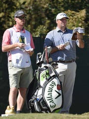 Jonathan Randolph and his caddy consult their notes