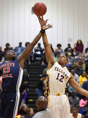 Forest Hill's Ladarius Marshall (23) jumps at center with Columbus Falcon Robert Woodard (12) during a Rumble in the South MLK Classic high school basketball tournament game on Monday, January 15, 2018, at St. Andrew's Episcopal School in Ridgeland, Miss.