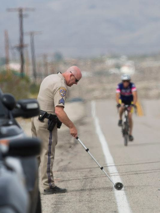 California Highway Patrol investigator takes measurements at the scene where a vehicle struck two cyclists participating in the 2018 Tour de Palm Springs near Indio Hills, Calif., Saturday, Feb. 10, 2018. Police say the car seen was driving down a road at twice the speed limit colliding into cyclists participating in the 100-mile charity bike ride. (Omar Ornelas/The Desert Sun via AP )
