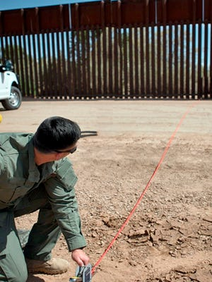 In this April 14, 2016, file photo provided by U.S. Customs and Border Protection, a Border Patrol agent shows the path of a tunnel that crosses the U.S.-Mexico border near Calexico, Calif. The federal government has started work on a border wall in California to replace a decades-old decaying barrier.