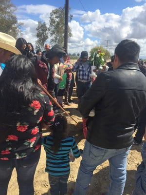 Farmworkers hold a vigil in Delano, CA., for a couple that who died after losing control of their sport utility vehicle and crashing into a power pole as they fled immigration officials in a rural California farm town.