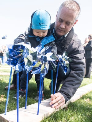 Ross County Prosecutor Matt Schmidt and his son Calvin plant pinwheels at the entrance to Yoctangee Park on Thursday. Each of the 1,052 pinwheels represent a case of confirmed child abuse and neglect  in Ross County in 2017.