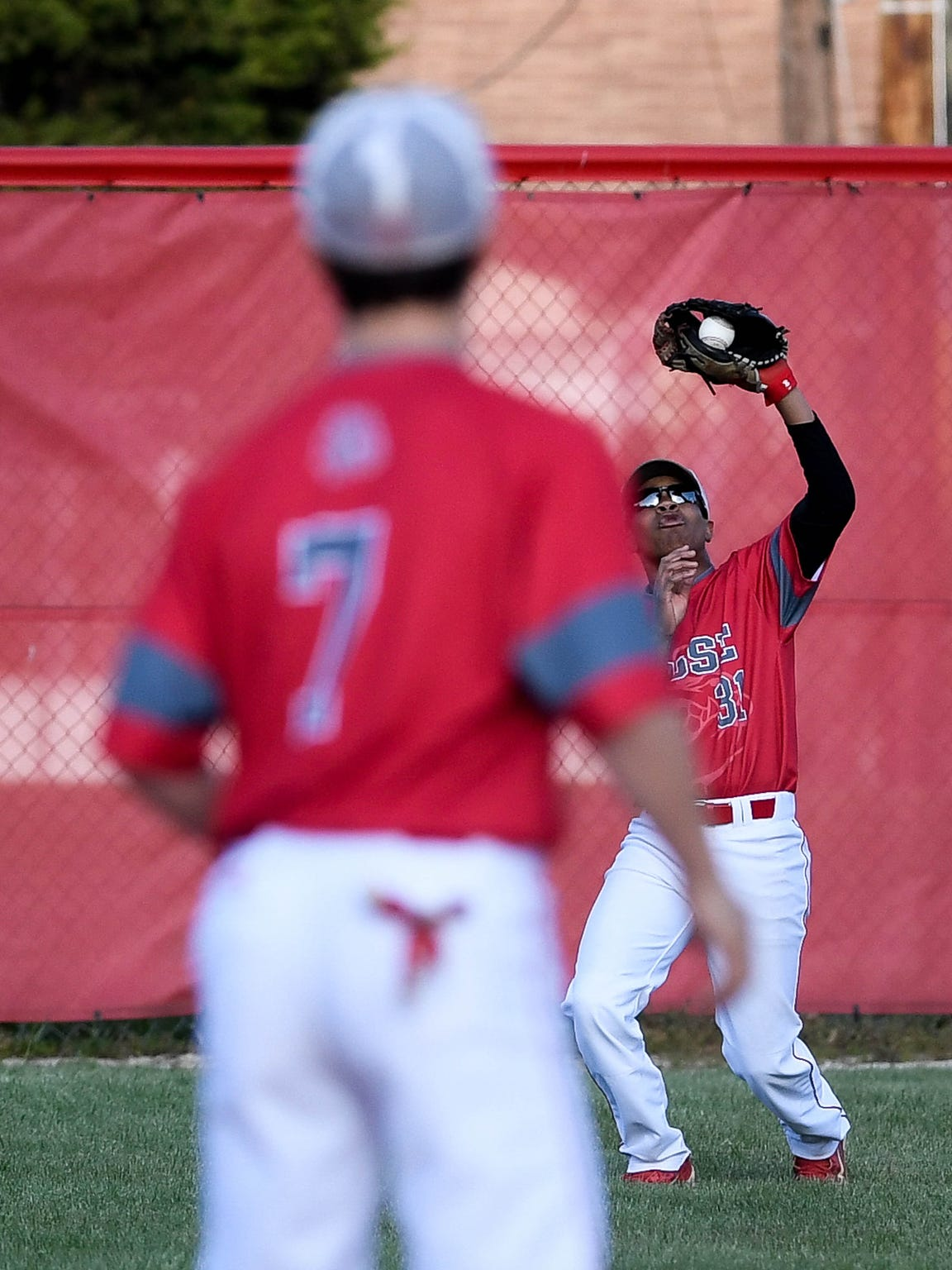 Bosse outfielder Michael Roach (31) makes a catch as teammate Reid Stevens (7) looks on as the Bulldogs faced Castle on Thursday night at Washington Avenue Field.