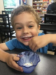 Lincoln Copeland enjoys ice cream at Lofty Pursuits. July is National Ice Cream Month.