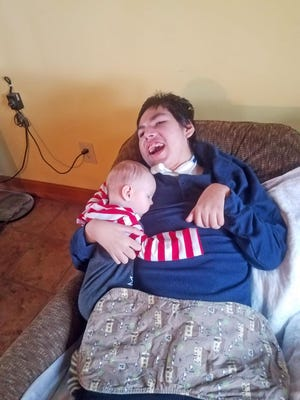 Dwight Green, 13, holds his nephew, Liam. Dwight has a traumatic brain injury and requires near round-the-clock care. That does not stop him from expressing his love for his family members.